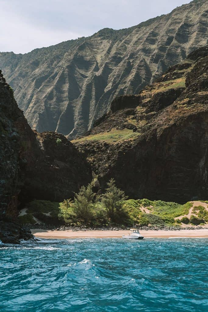 Boat docked on a pristine beach on the Na Pali Coast in Kauai