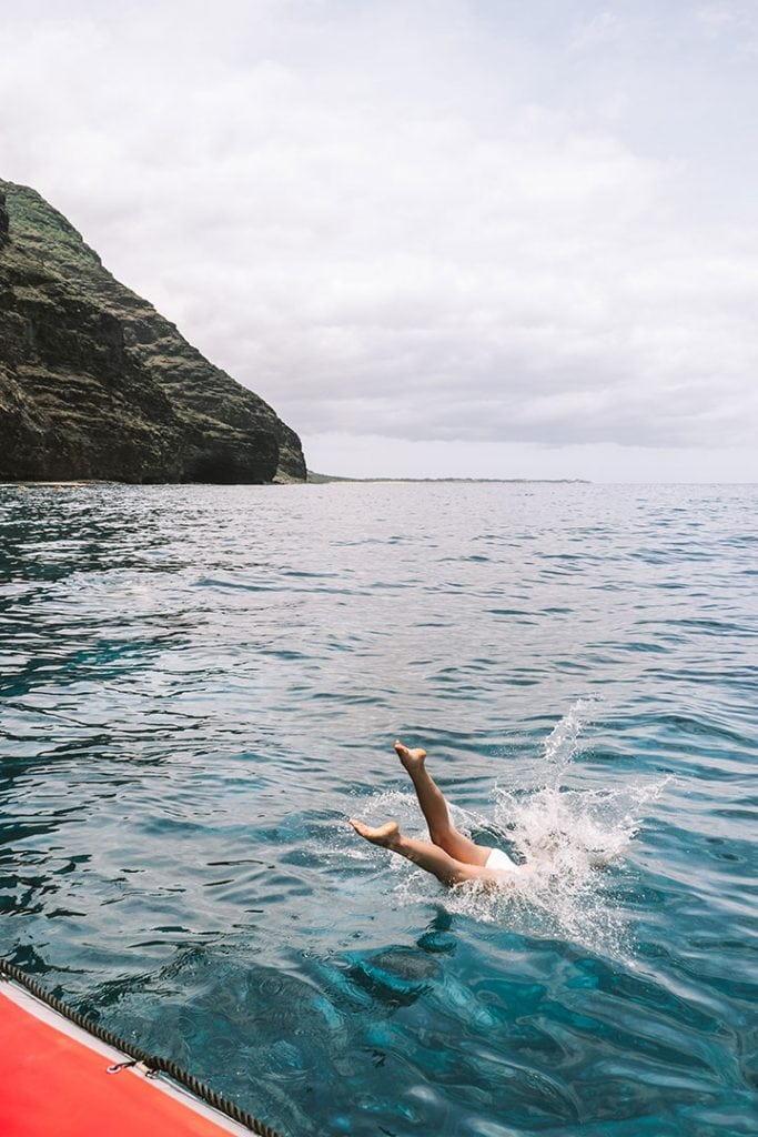 Girl Diving into Ocean with Kauai's Na Pali Coast in background