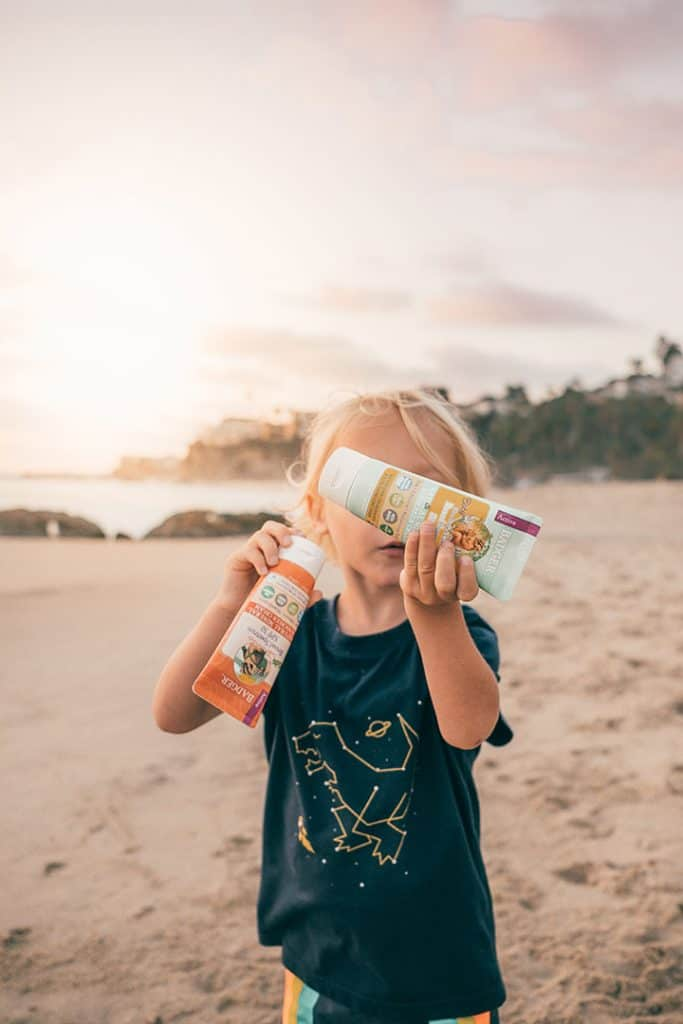 Boy holding Kids Badger Sunscreen on the Beach | Natural Reef-Safe Suncreen
