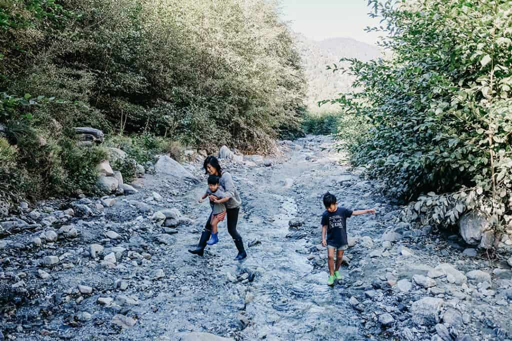 Family crossing creek in Forest Falls, California
