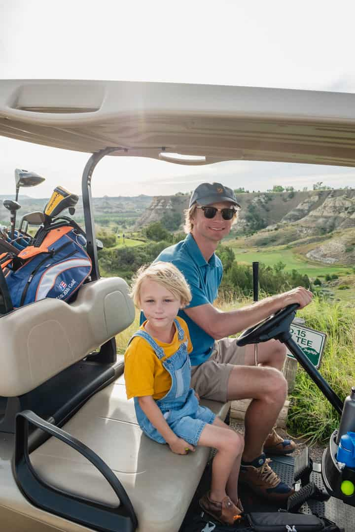 Father and son golfing at Bully Pulpit Golf Course in Medora